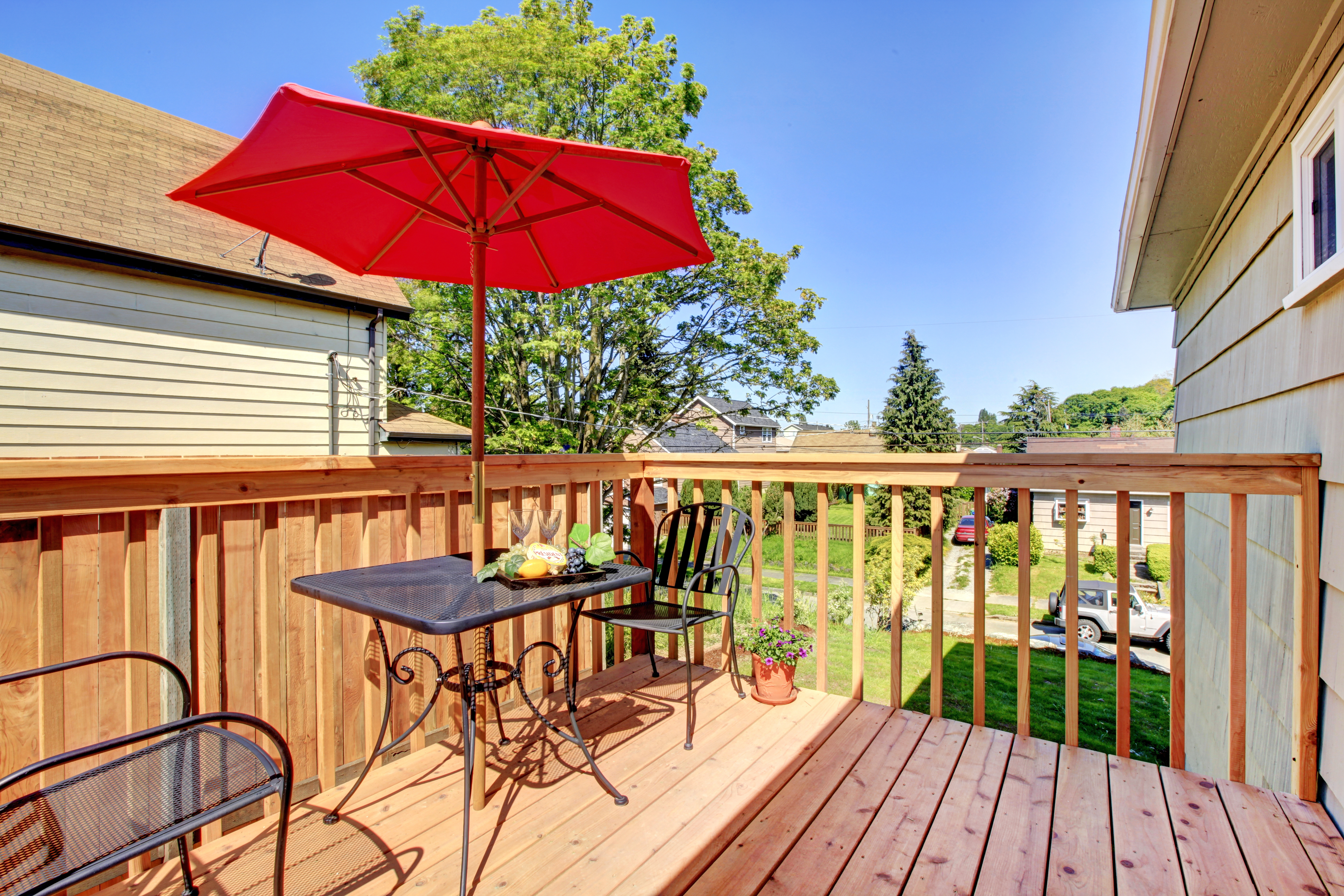 Deck with red umbrella with warm wood.